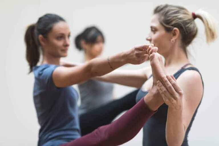 Yoga teacher assisting student